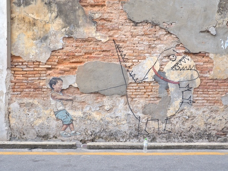 Penang, Malaysia - May 11, 2017: Little Boy with Pet Dinosaur, street art  painted by Ernest Zacharevic in Georgetown city, Penang, Malaysia.