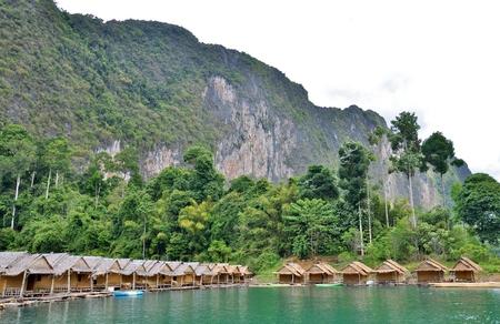 De traditionele Thaise toevlucht die van het bamboehuis, onder bergenmening, duidelijke hemel en duidelijk water in de Cheow Lan-Dam (Ratchaprapa-Dam) drijven bij het Nationale Park van Khao Sok, de Provincie van Surat Thani, Thailand. Stockfoto - 84720075