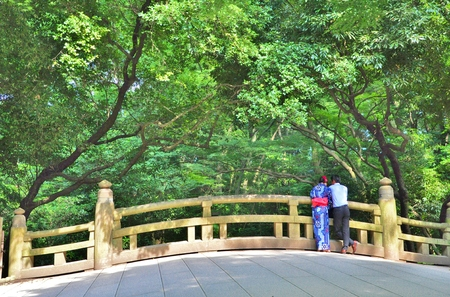 Rear view of Japanese couple standing on the bridge in the garden with the tree background. A man wears blue shirt with slacks, a woman wears Yukata. Love and nature concept.