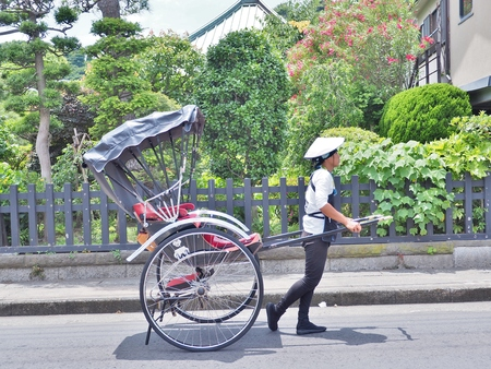 Kanagawa, Japan - June 09, 2017: The rickshaw-man on the street in Kamakura, Japan. A rickshaw is a man-powered car, made for two people. Sightseeing on a rickshaw is a staple attraction in Kamakura.