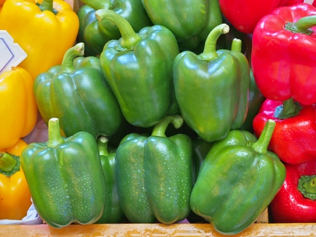 Ripe Yellow, Red and Green Peppers in wooden box at vegetables market.