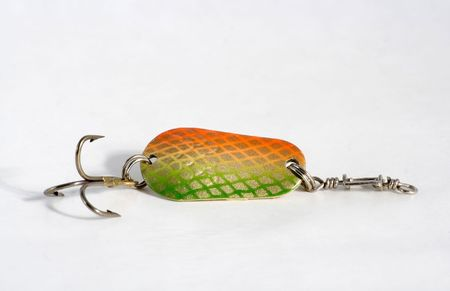 Spoon bait is dyed green color with hook on white background photo