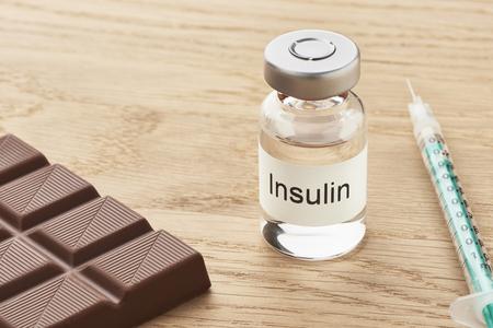チョコレートのテーブルの横に注射器とインスリン アンプル