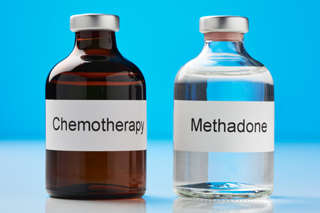 A ampoule of methadone and a chemotherapy stand on white surface against blue background (English label in transverse format)