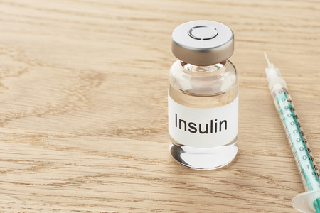 Insulin ampoule and a syringe lie on a wooden table