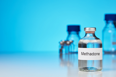 A ampoule of methadone stands on white surface against blue background on the right. Further laboratory bottles can be seen in the background. (English lettering)transverse format with space for text