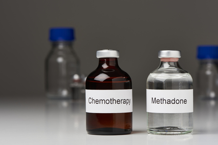 An ampoule of methadone and a chemotherapy stand side by side on white surface against gray background. Further laboratory bottles can be seen in the background. (English inscription) in cross-format
