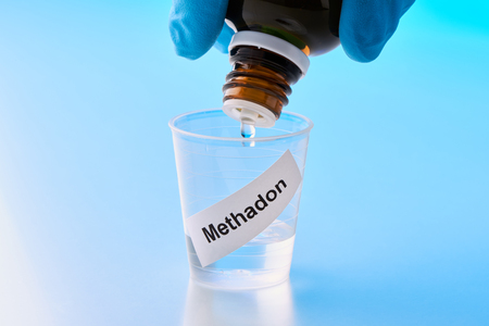 methadone is dropped into a beaker. The inscription on the mug is German Stock Photo