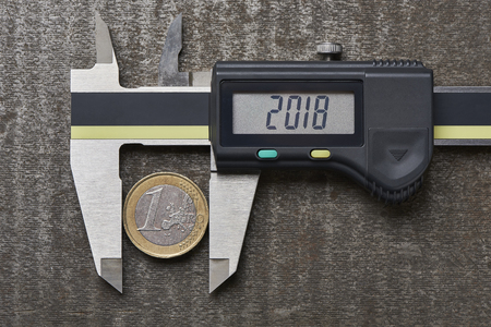Economy in 2018 - financial evaluation in the industry - measurement of a euro coin with a measuring slider on the display is the year 2018