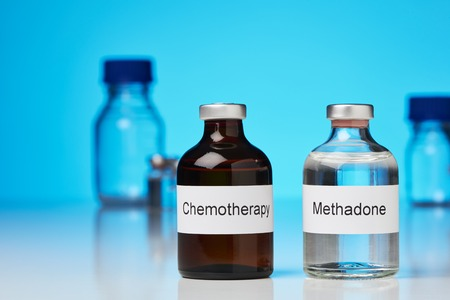 An ampoule of methadone and a chemotherapy stand side by side on white surface against a blue background. Further laboratory bottles can be seen in the background. (English inscription) in cross-format
