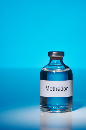 A bottle of methadone stands in the spotlight on a white surface. The Hitergrund Lights blue. The label is labeled in German