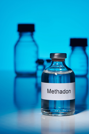 A vial of methadone stands on a white surface against a blue glowing background. The ampoule is lit by a spot light. The label is in German. In the background are more bottles