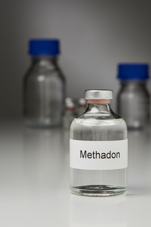 a bottle with methadone stands on a white surface in front of gray dark background. The label is in German. In the background are more laboratory bottles