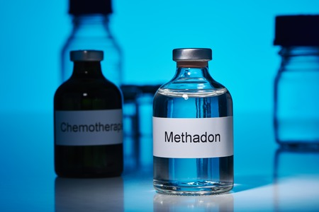An ampoule of methadone stands on a laboratory bench. The ampoule is in the spotlight. A little further back is an ampule standing on the chemo. The background is glowing blue. The labels are labeled in German. Stok Fotoğraf