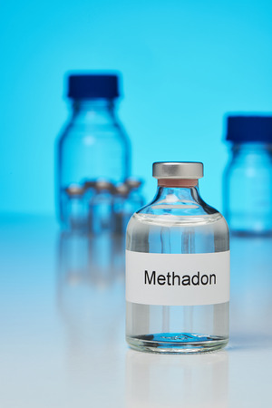 A bottle of methadone stands on a white surface against a blue glowing background. The Ettiket is labeled in German. In the background are further laboratory bottles Stock Photo