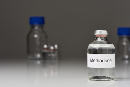 An ampoule of methadone stands on a white surface against a gray background. The ampoule is on the right side. In the background are more lab bottles. The label is in English. The picture is in landscape mode