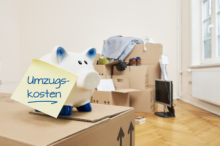 On a moving box there is a piggy bank with a yellow note sticking to it. On the note is in German relocation costs. In the background is a stack of packed moving boxes