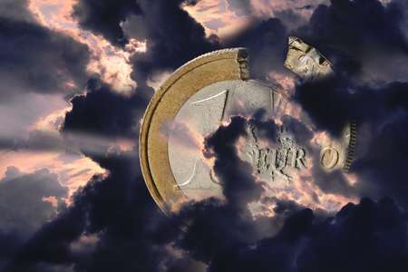 A damaged Euro coin shrouded in bad weather clouds. The clouds are dark and glow red in the background. The European Union in the Kriese
