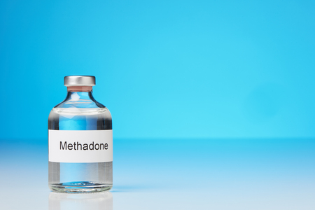 An ampoule of methadone is on the left in the picture. The background is blue. The label on the ampoule is labeled in English with methadone. There is space for text on the right side of the picture