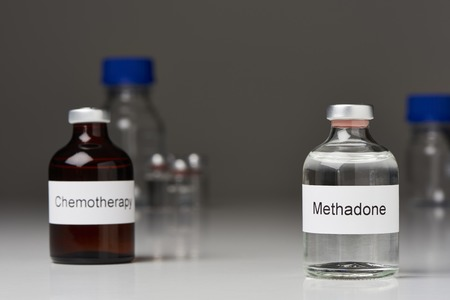A ampoule of methadone (right) and a chemotherapy (left) stand on a white surface against a gray background. Further laboratory bottles can be seen in the background. (English inscription) in cross-format