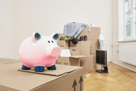 移動 - 左前にピンクの貯金箱が立っている移動ボックスです。部屋の後ろの部分には、パックされた移動ボックスのスタックです 写真素材