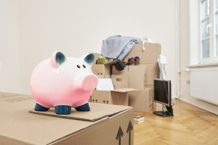 Moving - At the front left is a moving box on which a pink piggy bank stands. In the back part of the room is a stack of packed moving boxes 스톡 콘텐츠