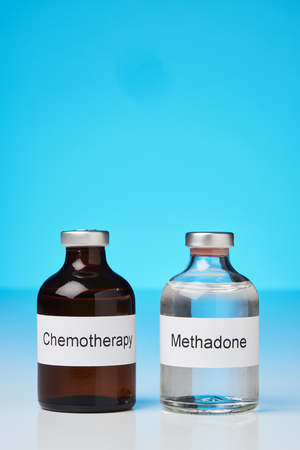 An ampule of methadone and chemo are standing on a white surface against a blue background. Stock Photo