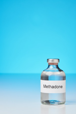 Substitute drug methadone. On the right is a vial of methadone. The background is blue. The label says in English methadone (methadone) Stock Photo