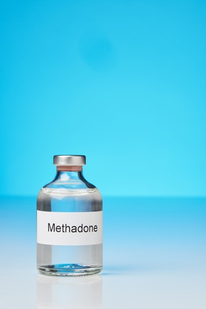 An ampoule of methadone stands on a white surface against a blue background on the left side. (English caption) in portrait format with plenty of free space for text. The label is in English
