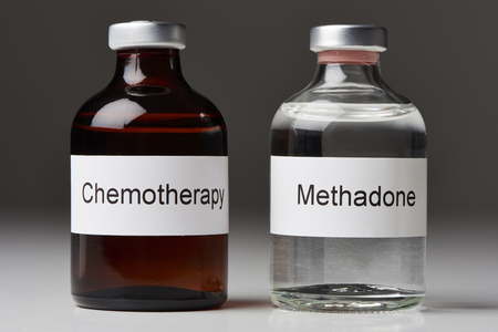 An ampoule of methadone and a chemotherapy stand on white surface against gray background (English label in transverse format) Stock Photo