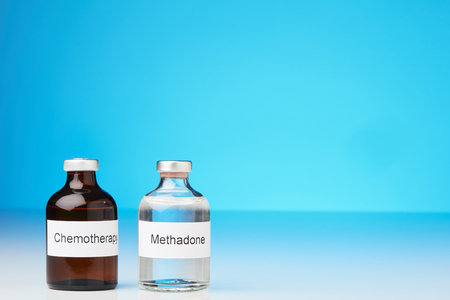 An ampoule of methadone and a chemotherapy stand on white surface against a blue background at the left side of the image (English label in transverse format)