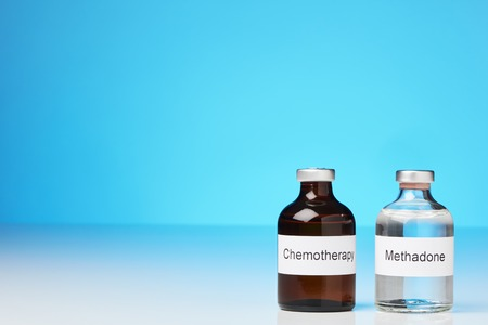 An ampoule of methadone and a chemotherapy stand on white surface against a blue background at the right side of the image (English label in transverse format) Stock Photo
