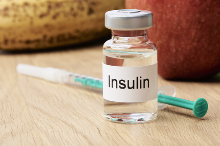 Insulin - A vial of insulin is on a table and next to it is an syringe. In the background are an apple and a banana