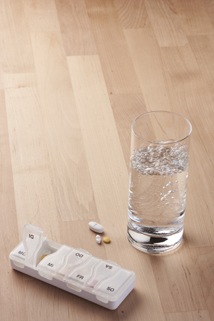 Medication - taking tablets with water - next to a glass of water are a few tablets and a tablet container Stok Fotoğraf