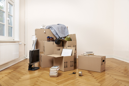 Packed moving cartons in the living room of the rented apartment. With wooden floor. Large window on the left Stockfoto