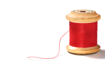 a spool of thread with red yarn isolated against white background