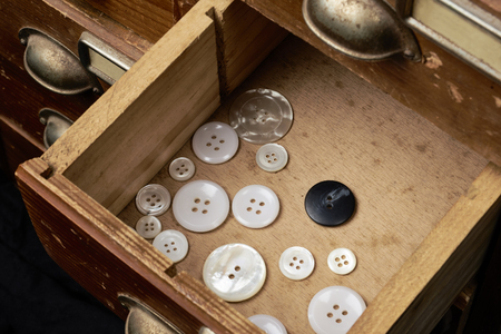 An open drawer with some buttons. One button is differentiated from the other because it is different. Example of the exclusion of foreigners in the society Stok Fotoğraf