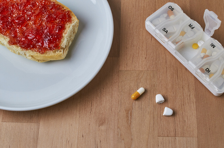 Taking medication: A breakfast plate with a bread roll with jam next to leagues different tablets Stok Fotoğraf