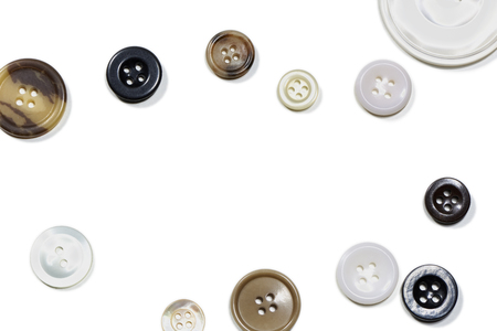 Several old buttons isolated in front of white background. In the middle is space for text or a logo for a flyer or a card Stok Fotoğraf