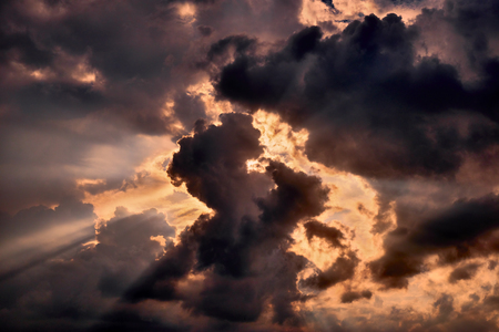 Dramatic cloudscape in front of the orange glowing summer evening sun