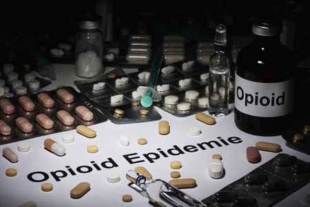 In the dark you can see an ampoule Opioid next to it is a note written in German Opioid epidemic. All around, many tablets and syringes are scattered. Stok Fotoğraf