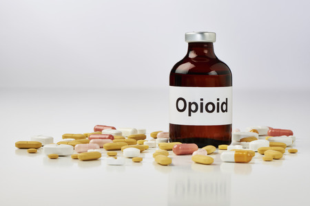On a white surface stands an ampoule on which opioid is written. There are many tablets around the ampoule. The background is white Stok Fotoğraf