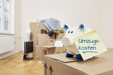 Moving expenses! A piggy bank with a yellow note on which is written in German moving expenses. The piggy bank is standing on a moving box. In the background are packed moving boxes. Stock Photo