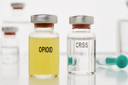 An ampoule with opioid it is an ampoule with the inscription Crisis. In the background are more ampoules and a syringe to see Stok Fotoğraf