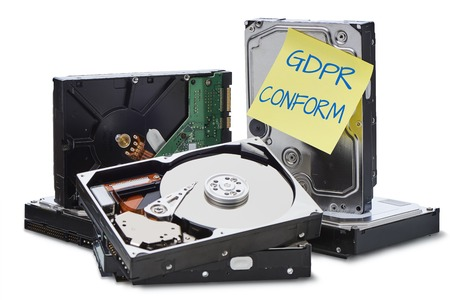 GDPR  Several hard disks stacked on top of each other. On a hard disk is a yellow note on which is written in English conform