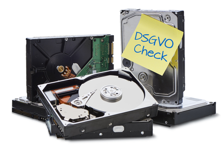 DSGVO  Several hard disks stacked on top of each other. On a hard disk is a yellow slip on which is written in German language DSGVO Check