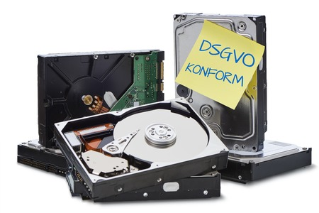 DSGVO  Several hard disks stacked on top of each other. On a hard disk is a yellow note on which is written in German language conform