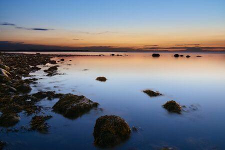 Beautiful sunset on a stony beach on the German Baltic Sea coast. On the beach of Wangels in Ostholstein
