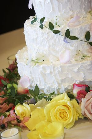 A photo of a wedding cake, just a detail shot with some flowers in the foreground and an unlit candle Stock Photo - 593746