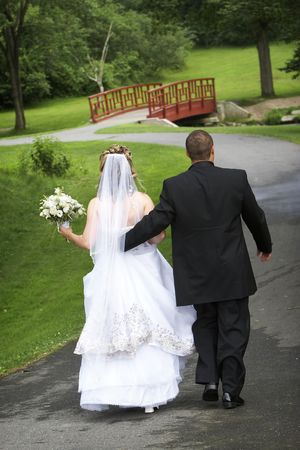 mate married: Bride and Groom holding hands walking away from the camera towards a bridge, along a paved path Stock Photo